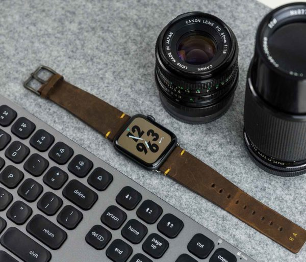 Old-Brown-AW-vintage-brown-band-with-monogram-close-to-a-set-of-camera-lens