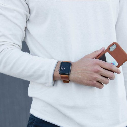 Tawny-Apple-watch-full-grain-brown-band-matches-barrel-Iphone-leather-case-on-top-of-white-shirt-bs