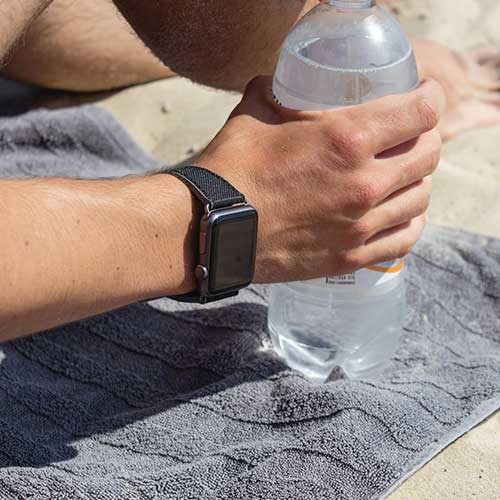 Gloomy-Apple-watch-black-natural-rubber-band-close-up-drinking-on-the-beach-in-a-sunny-day-ig