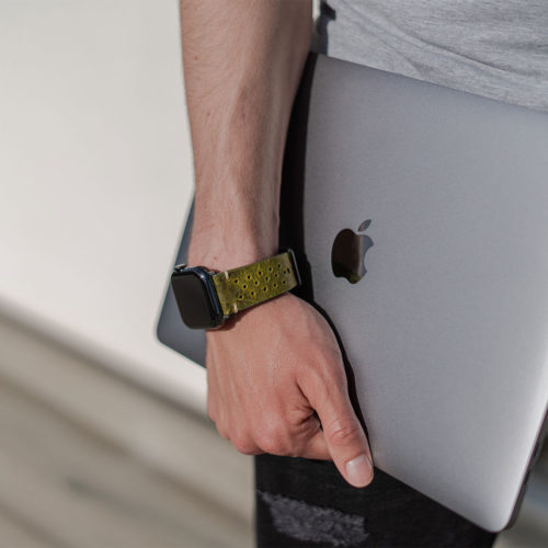 AW-bullet-proof-green-leather-band-handling-a-silver-macbook