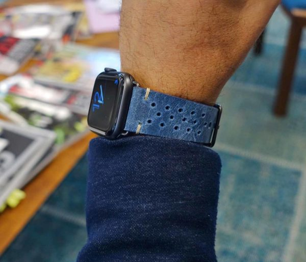 Breathe-AW-blue-calf-leatehr-band-with-30-holes-on-wrist-close-to-a-blue-jacket