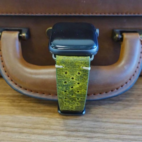 Hope-AW-green-calf-leatehr-band-with-30-holes-front-of-a-leather-luggage