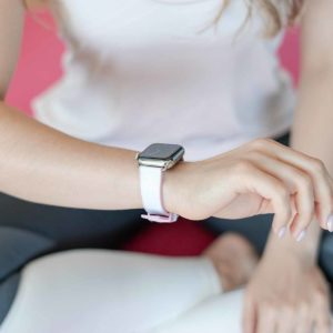 Pink Sand AW white rubber band on wrist of a woman runner with white shirt and a grey paint