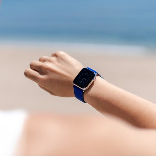 Blueberry Summer-Apple-watch-blue-fluo-band-on-a-feminne-tunned-wrist-with-the-sea-as-background