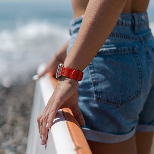 Apple-watch-orange-tide-band-recycled-ocean-plastic-woman-with-a-paddle-surf-going-to-sea