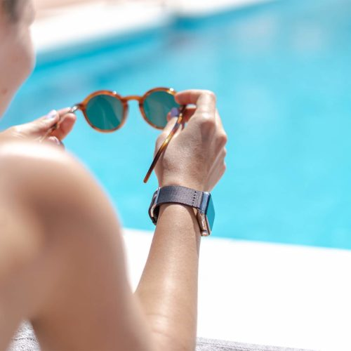 Apple-watch-black-tide-band-recycled-ocean-plastic-woman-handles-own-eyewear-close-to-a-swimming-pool