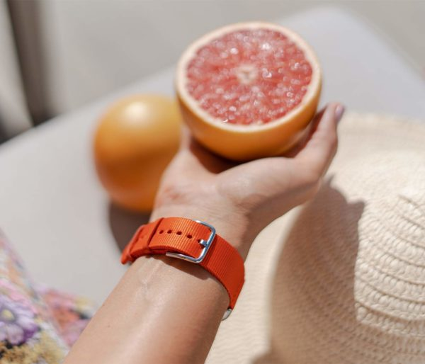 Apple-watch-orange-tide-band-recycled-ocean-plastic-woman-handling-a-grapefruit-on-back-side